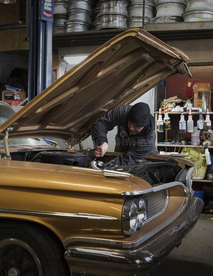 Работник автоматического магазина исправляя винтажный автомобиль стоковое изображение rf