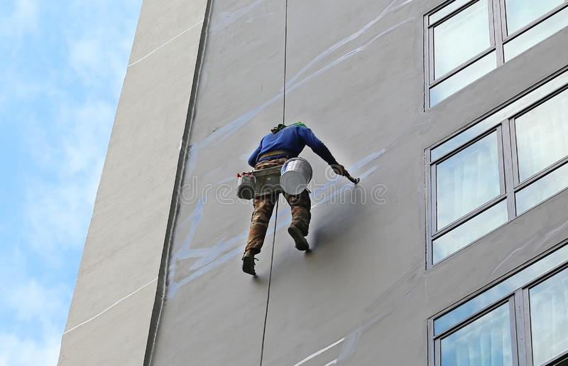 Работник альпиниста вися на веревочках для того чтобы отремонтировать обслуживание здания на высоком здании подъема стоковое фото rf
