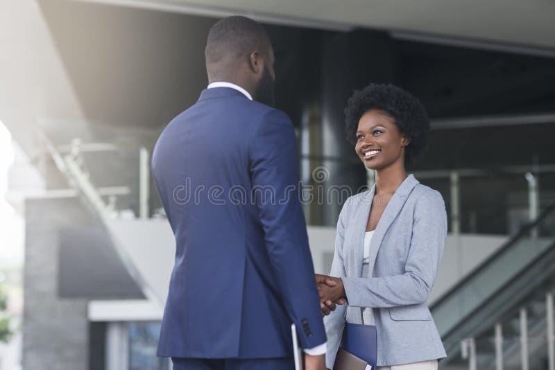 Работник африканского handshaking босса женский поздравляя ее с продвижением стоковые фото