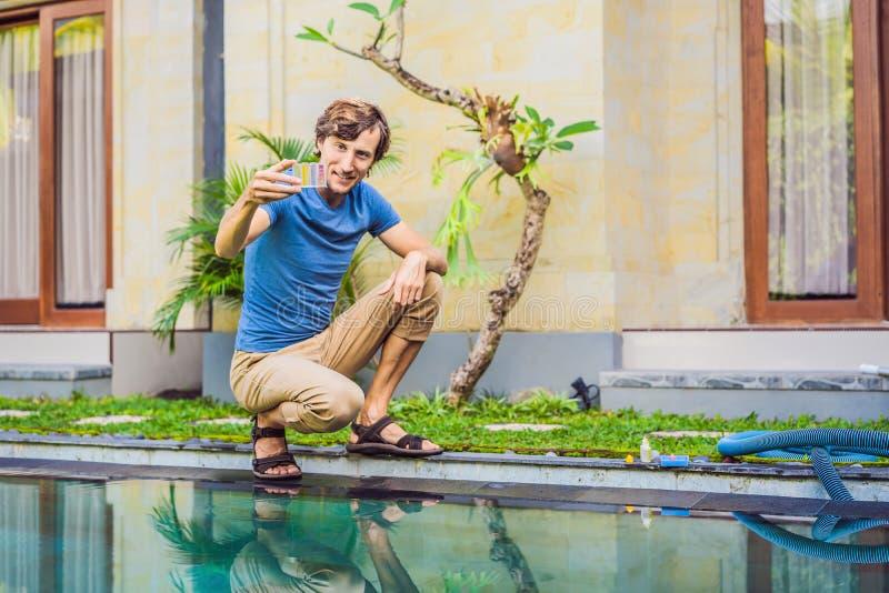 Работник бассейна проверяет бассейн для безопасности Измерение хлора и ПЭ-АШ бассейна стоковые фотографии rf