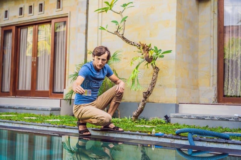 Работник бассейна проверяет бассейн для безопасности Измерение хлора и ПЭ-АШ бассейна стоковое изображение