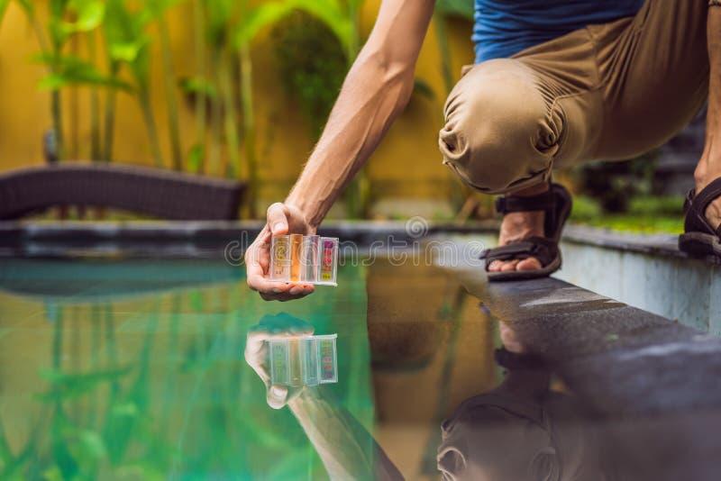 Работник бассейна проверяет бассейн для безопасности Измерение хлора и ПЭ-АШ бассейна стоковое изображение rf