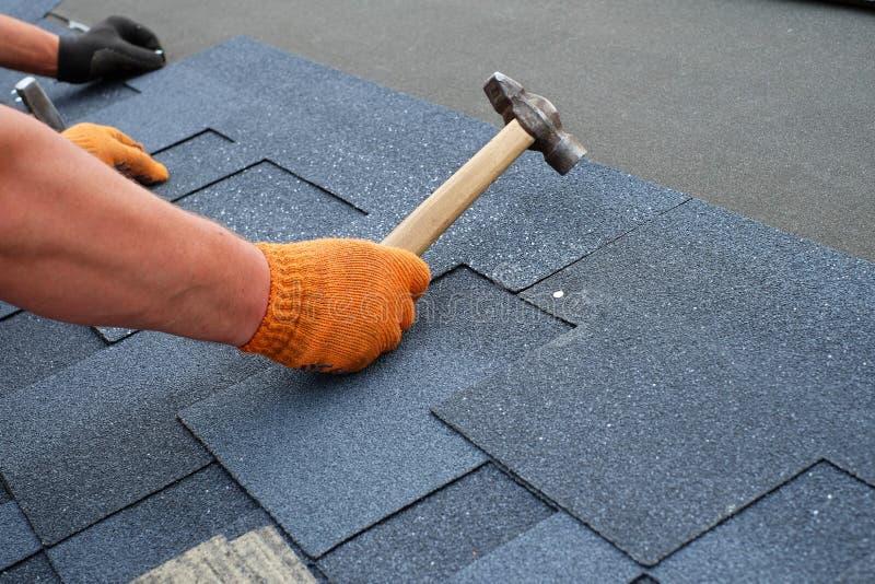 Работник вручает устанавливать гонт крыши битума используя молоток в ногти стоковые изображения