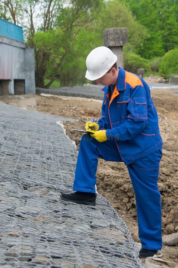 Работник в голубой форме, записывает конструкцию нового ландшафта, подготавливая усилить банки после затоплять стоковое изображение rf