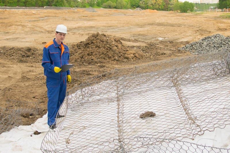 Работник в голубой форме и белом шлеме, с планшетом в его руках, контролирует конструкцию берега стоковое фото rf