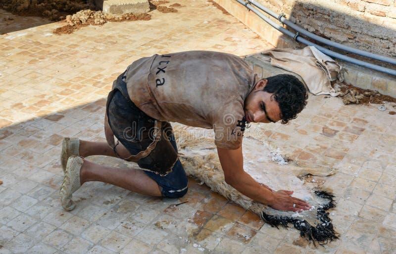 Работник в кожаной традиционной дубильне fez Марокко стоковое фото