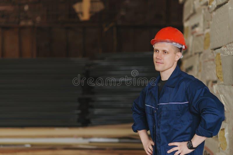 Работник в красных крышке и форме стоит против фона t стоковые фотографии rf