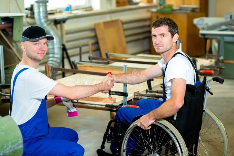 Работник в кресло-коляске в мастерской плотника с его colleagu стоковое изображение