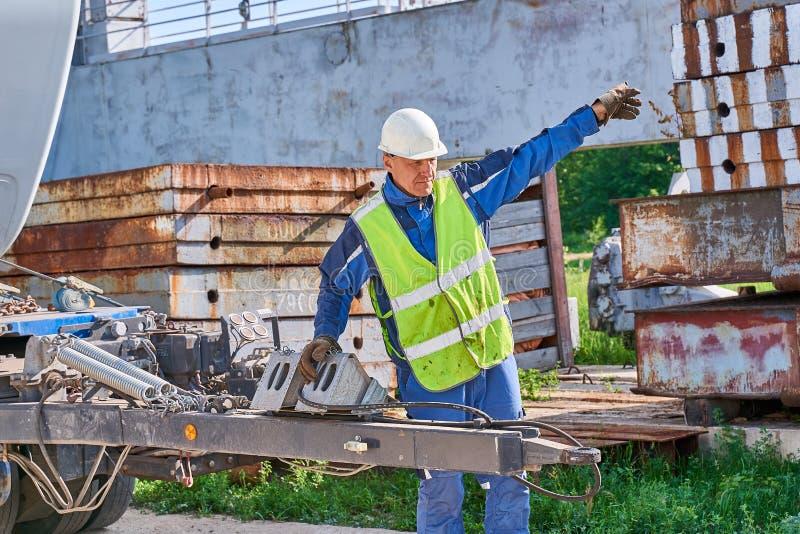 работник в шлеме и защитный жилет контролирует загрузку стоковые фотографии rf