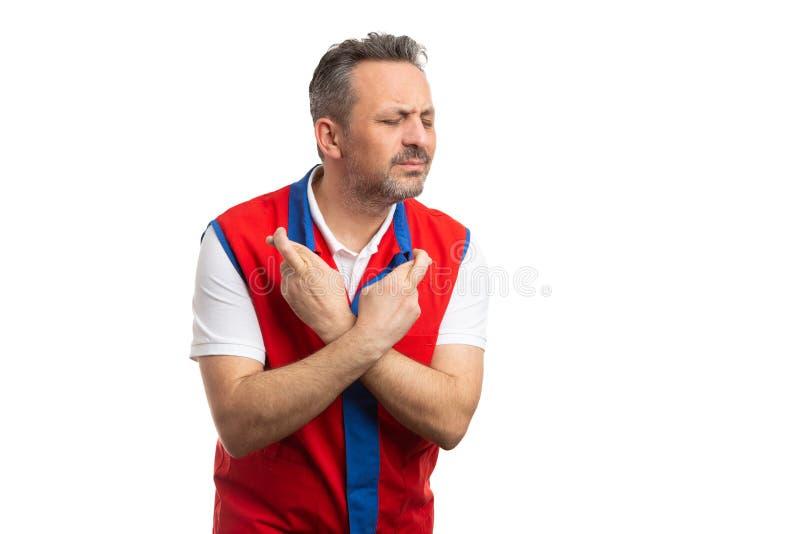 Работник гипермаркета держа пальцы пересеченный с надеющийся выражением стоковые изображения