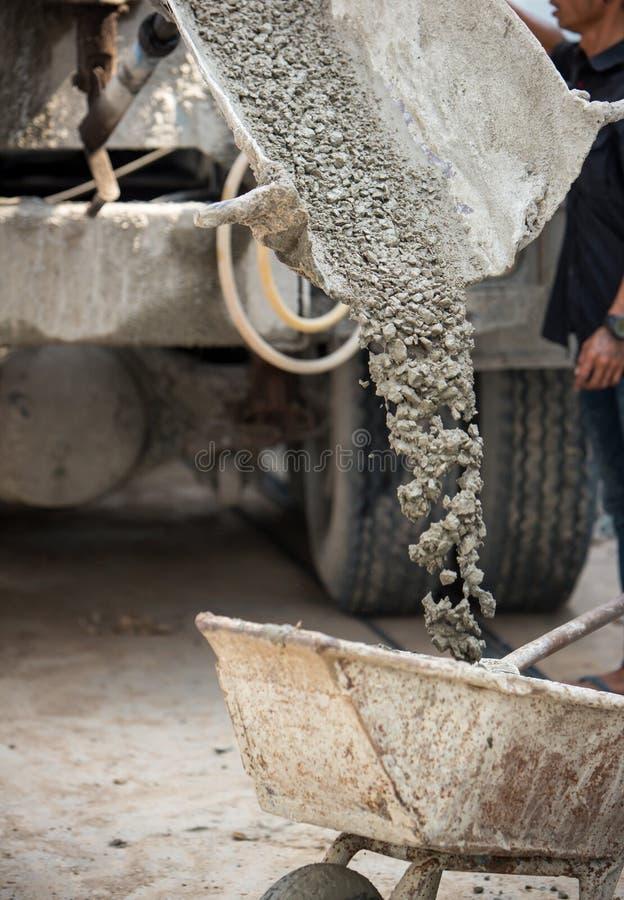 Работник держа вагонетку для поддержки лить Крит смешал тележку точильщика цементного раствора стоковая фотография rf