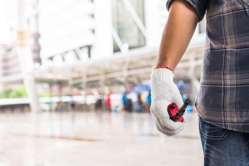 Работник держит красное walky talky правой рукой которая носящ стоковые изображения rf