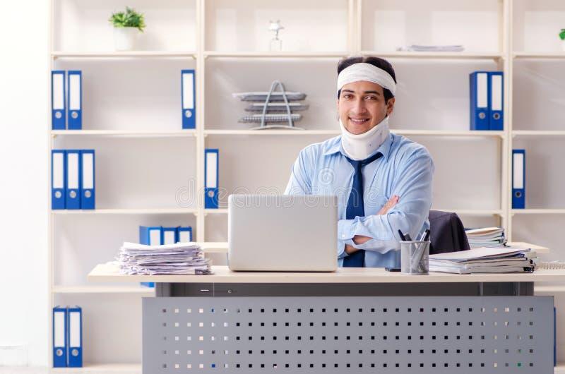 Работник детенышей раненый мужской работая в офисе стоковое изображение