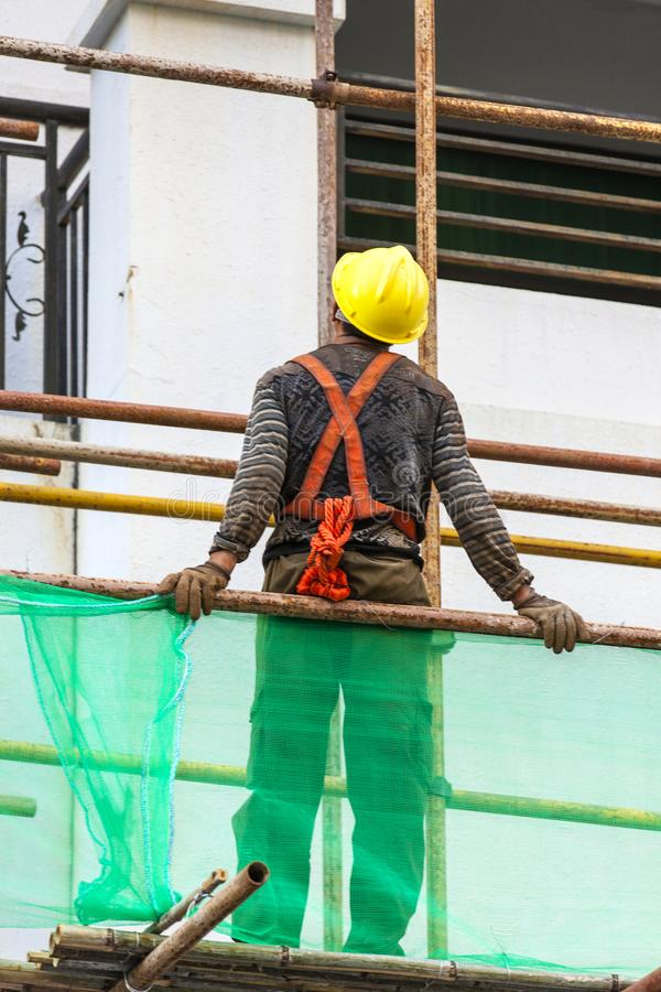 Работник для того чтобы раскрыть леса на строительной площадке стоковые изображения