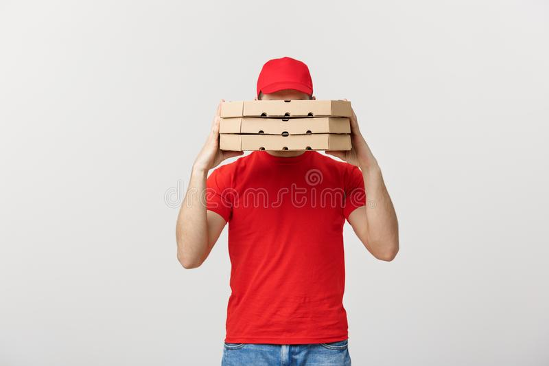 Работник доставляющее покупки на дом спрятанное за большим стогом коробок пиццы он носит Изолировано над серой предпосылкой стоковые изображения