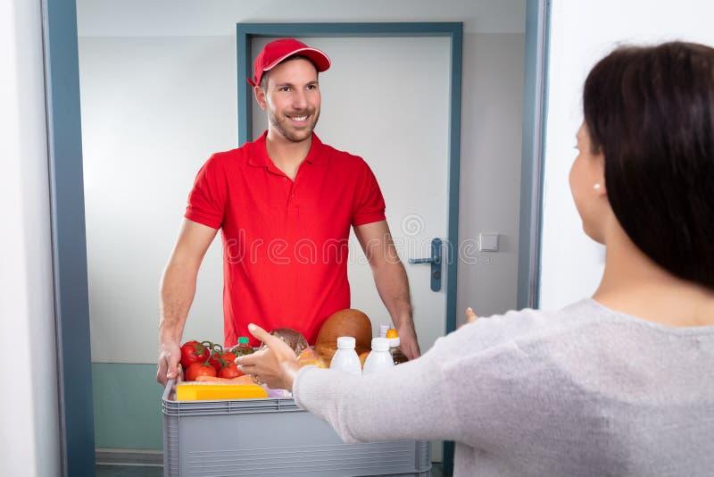 Работник доставляющий покупки на дом давая коробку бакалеи женщине стоковая фотография rf