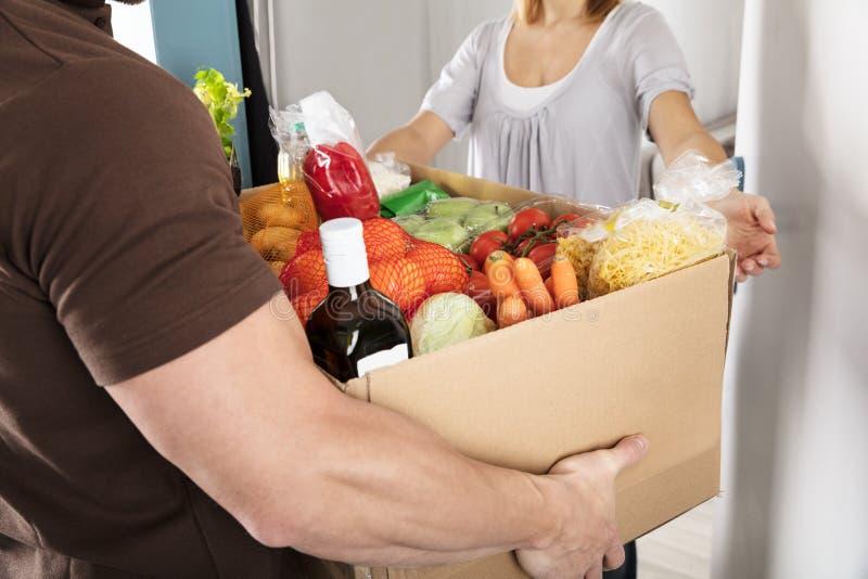 Работник доставляющий покупки на дом давая коробку бакалеи к женщине стоковые изображения rf