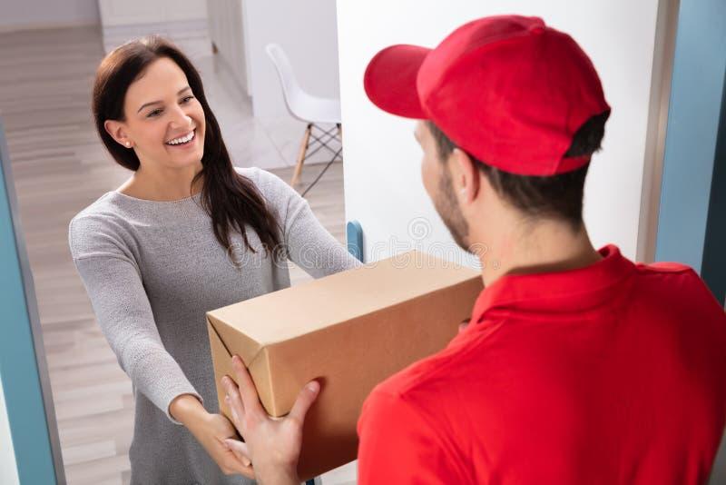 Работник доставляющий покупки на дом давая коробку молодой женщине стоковая фотография rf