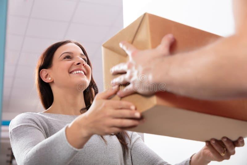 Работник доставляющий покупки на дом давая коробку молодой женщине стоковые изображения rf