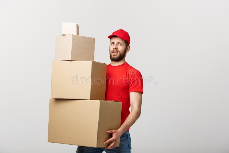 Работник доставляющий покупки на дом делая жест беспокойства держа картонные коробки стоковые изображения rf
