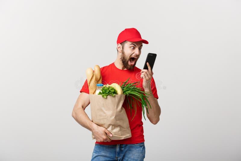 Работник доставляющий покупки на дом держа бумажную сумку с едой и ударом или сердитое с что-то в мобильном телефоне на белой пре стоковые фото