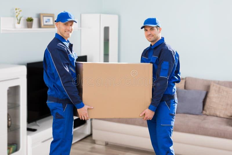 Работник доставляющий покупки на дом 2 держа картонную коробку стоковая фотография rf