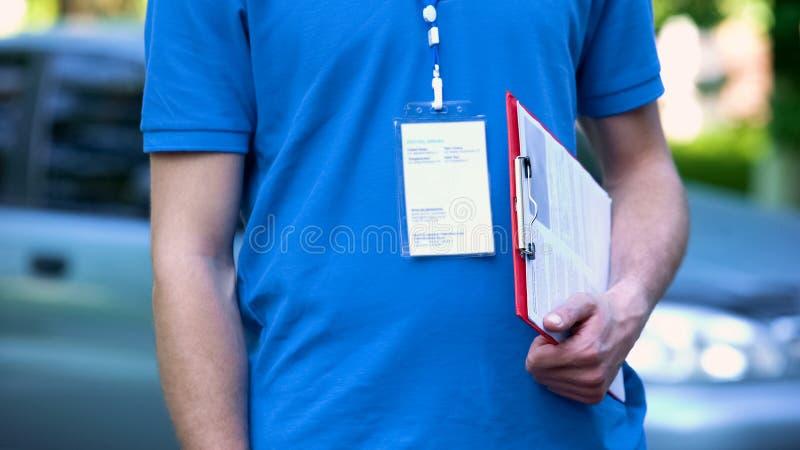 Работник доставляющий покупки на дом держа форму страхования, качественный сервис пересылки, срочную поставку стоковое фото
