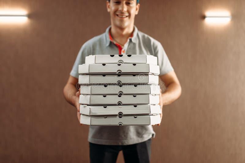 Работник доставляющий покупки на дом пиццы с коробками, поставляя обслуживание стоковые фотографии rf