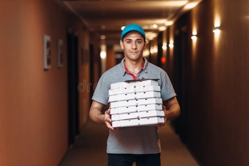 Работник доставляющий покупки на дом со свежей пиццей в коробках коробки стоковая фотография rf