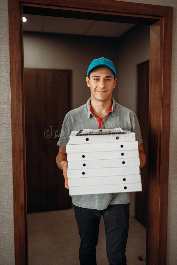 Работник доставляющий покупки на дом со свежей пиццей в коробках коробки стоковое изображение rf