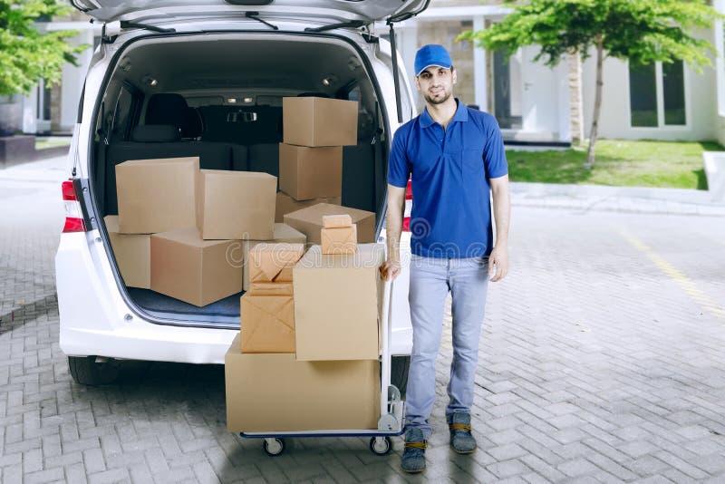 Работник доставляющий покупки на дом с вагонеткой и автомобилем стоковые изображения rf