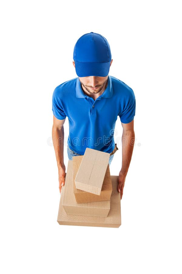 Работник доставляющий покупки на дом с коробками в голубой форме изолированной на белом backgr стоковое фото