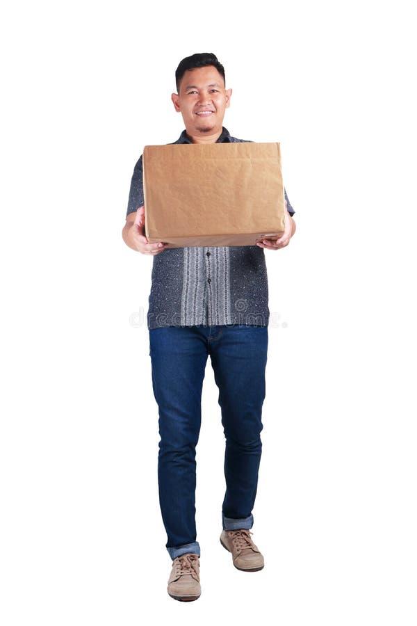 Работник доставляющий покупки на дом Courirer приносит коробку пакета стоковые фото