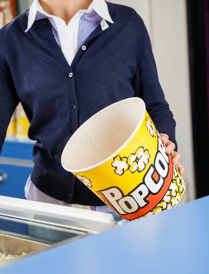 Работник держа пустое ведро попкорна на уступке стоковые фотографии rf