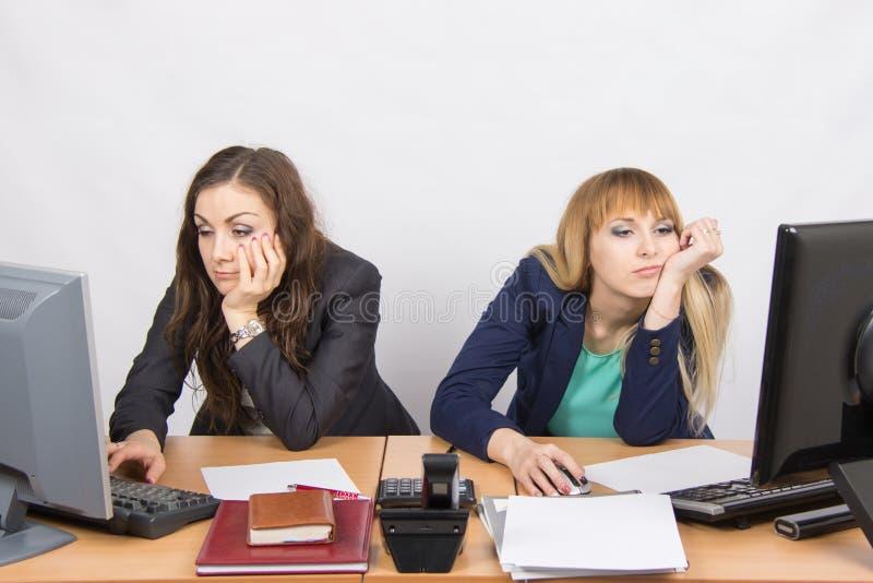 Работник 2 детенышей офиса за столом смотря уныло в рамку стоковое фото