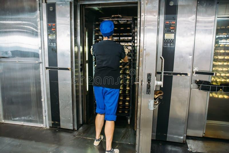 Работник женщины кладет подносы с печеньями в большую промышленную печь, фабрику кондитерскаи, продукцию печенья стоковая фотография