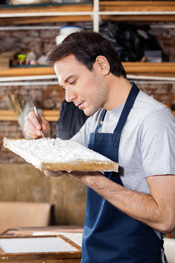 Работник извлекая грязь от бумаги в фабрике стоковые изображения