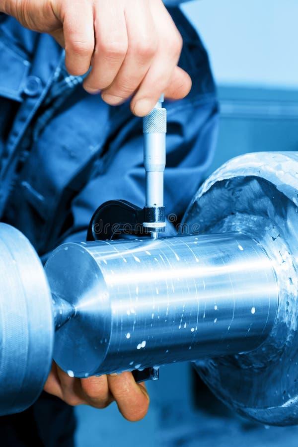 Работник измеряя на промышленной поворачивая машине Промышленность стоковые фото