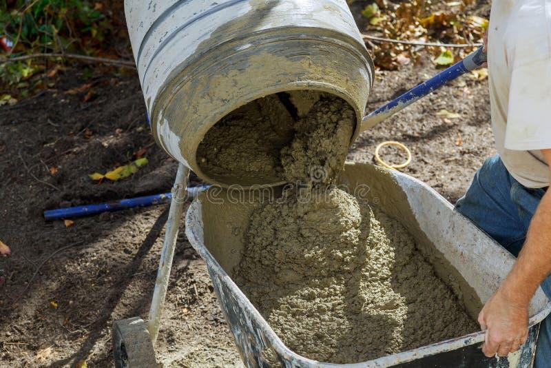 Работник использует бетон сделанный из в конкретного смесителя на работах строительной конструкции стоковые фото