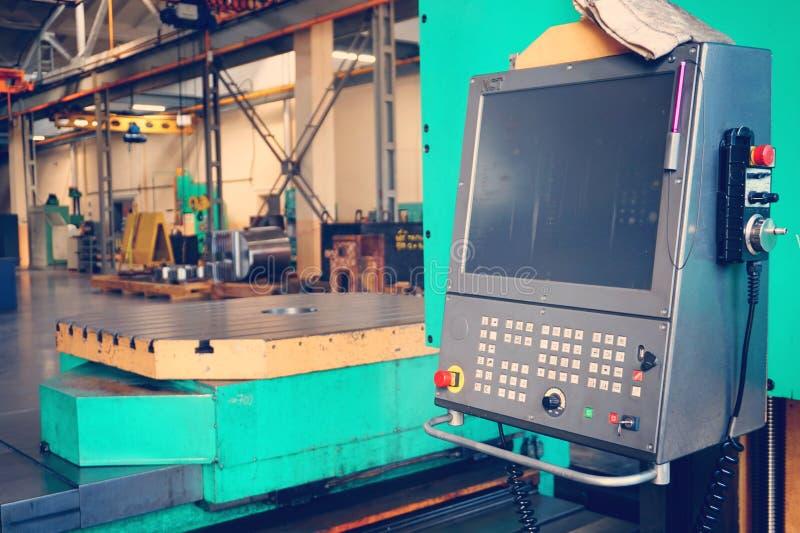 Работник использует пульт управления машины CNC для того чтобы обрабатывать материал стоковая фотография