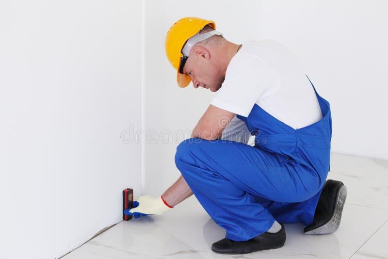 Работник используя линию уровень лазера стоковое фото