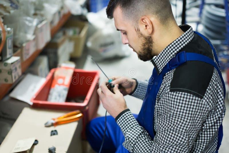 Работник используя его инструменты для ремонтировать штепсельную вилку стоковая фотография