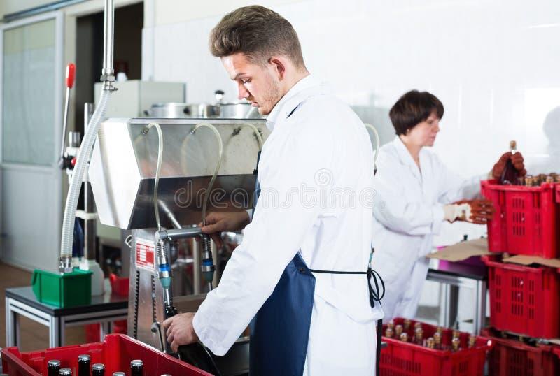 Работник используя машину для того чтобы разлить вино по бутылкам на фабрике игристого вина стоковые изображения rf