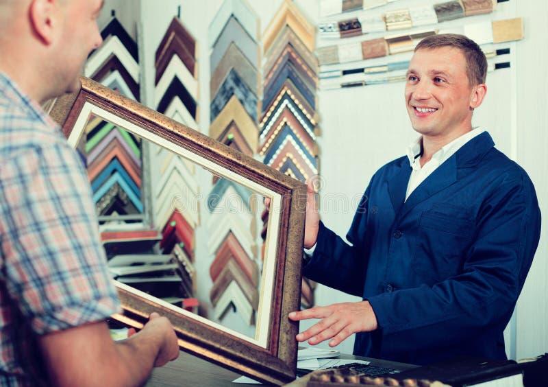 Работник и клиент в atelier рамок древесины стоковое изображение rf