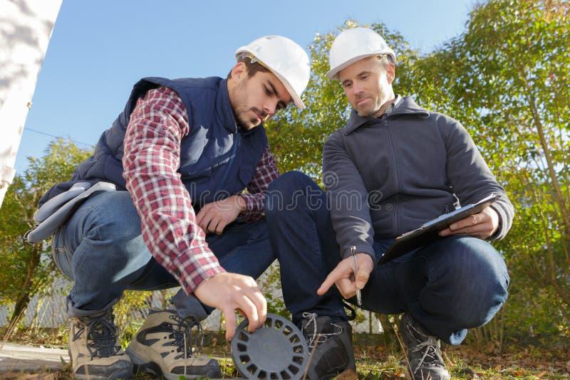 Работник и менеджер проверяя сток сточной трубы стоковая фотография rf