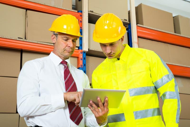 Работник и менеджер склада смотря компьтер-книжку стоковые фотографии rf