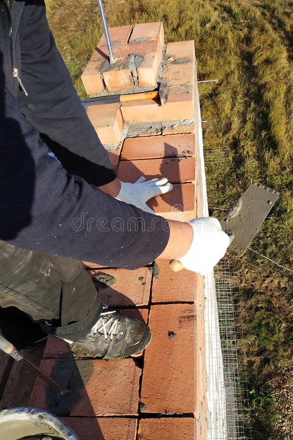 работник кладет кирпич на цементный раствор на предпосылке травы стоковые фото