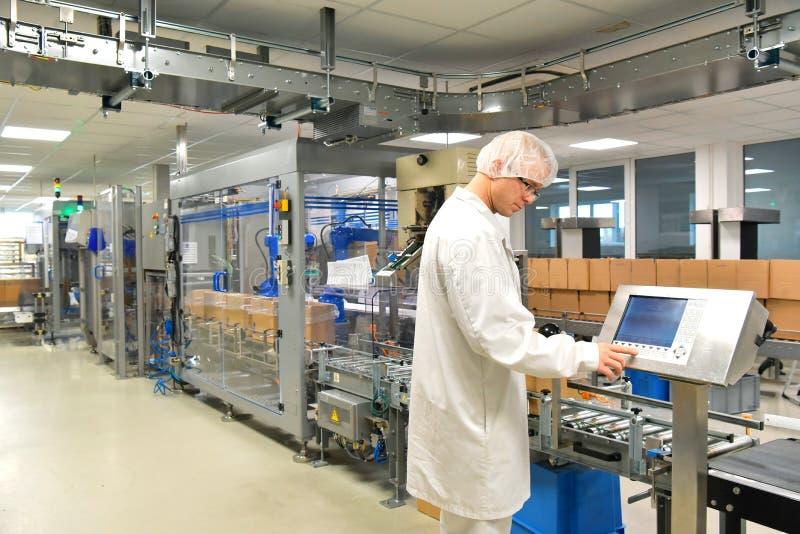 Работник конвейерной ленты приводится в действие робот который транспортирует ба инсулина стоковые изображения