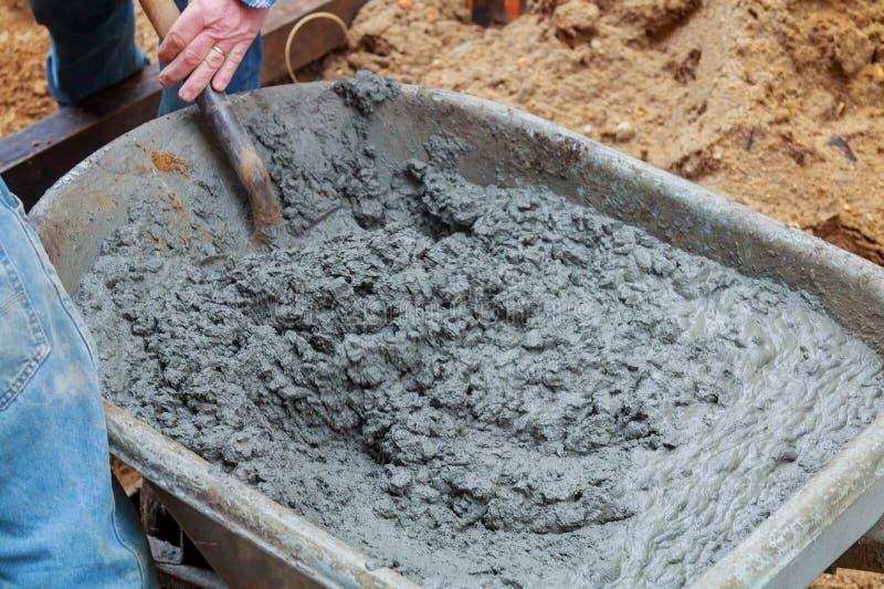 Работник копает влажное смешивание бетона от тачки на установке блока обочины стоковое фото rf