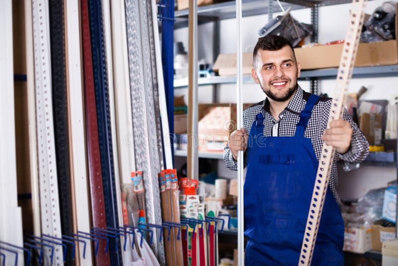 Работник молодого человека рассматривая пластичные углы для плиток и полов стоковое изображение